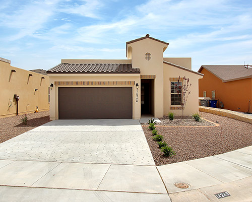 Single story stucco home with desert plants in the front yard.