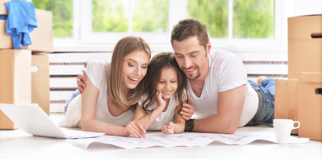 a happy young family looking up new homes for sale
