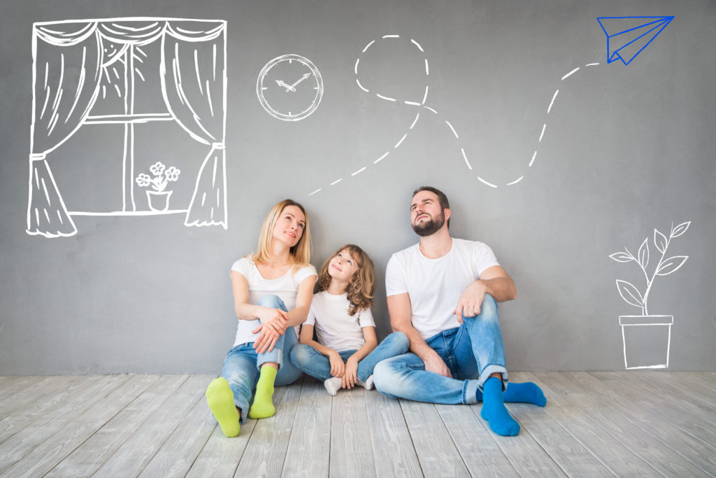 Happy family sitting on wooden floor. Father, mother and child having fun together thinking about their new home design.